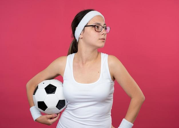 Pewna siebie młoda sportowa kobieta w okularach optycznych nosząca opaskę i opaski na rękę trzyma piłkę i patrzy na bok na białym tle na różowej ścianie