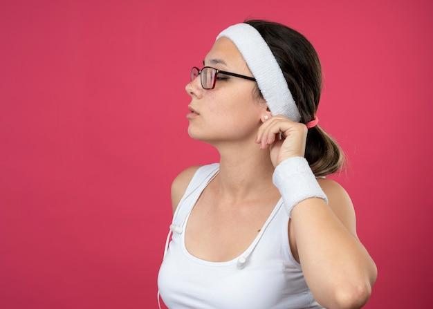 Pewna siebie młoda sportowa kobieta w okularach optycznych ze słuchawkami na sobie opaskę i opaski na nadgarstek trzyma ucho i patrzy na bok na białym tle na różowej ścianie