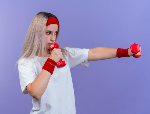 Pewna siebie młoda sportowa kobieta z szelkami na sobie opaskę i opaski stoi bokiem, trzymając hantle na białym tle na fioletowej ścianie