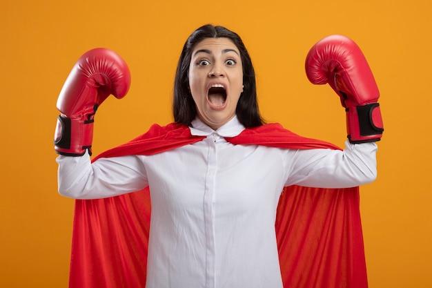Pewna siebie młoda superwoman w rękawiczkach pudełkowych, patrząc na przód, robi silny gest krzyczący na białym tle na pomarańczowej ścianie