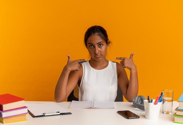 Pewna siebie młoda uczennica siedząca przy biurku ze szkolnymi narzędziami wskazuje na siebie