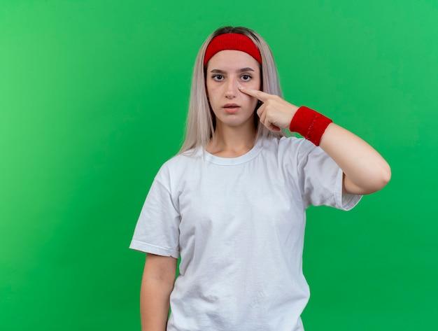 Pewna siebie młoda wysportowana kobieta z szelkami i opaską na nadgarstek ściąga powiekę patrząc na przód odizolowany na zielonej ścianie