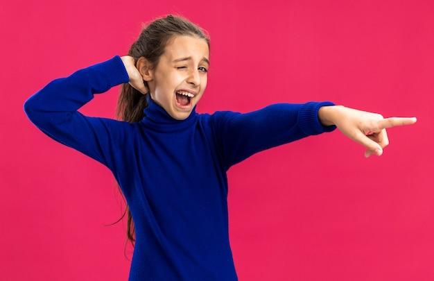Pewna siebie nastolatka trzymająca rękę za głową, mrugająca, wskazująca na bok odizolowana na różowej ścianie