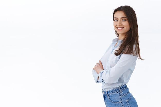 Pewna siebie, odnosząca sukcesy bizneswoman stojąca jak profesjonalistka, uśmiechnięta zadowolona, stojąca w profilu w pobliżu białej przestrzeni kopii i odwracająca się twarzą do znanego wyrazu twarzy, biała ściana