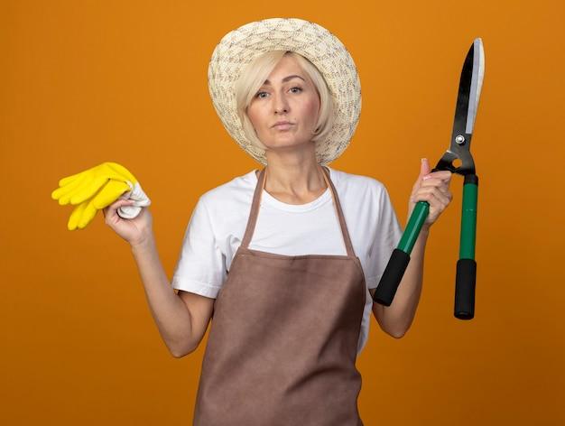 Pewna siebie ogrodniczka w średnim wieku w mundurze ogrodnika w kapeluszu, trzymająca rękawiczki ogrodnicze i nożyce do żywopłotu