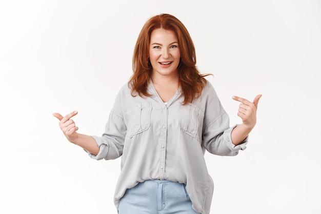 Pewna siebie optymistyczna triumfująca szczęśliwa rudowłosa kobieta w średnim wieku wskazująca się dumnie uśmiechnięta, ząbkowana kamera chwali się własnymi osiągnięciami wygrana na loterii zadowolona, biała ściana