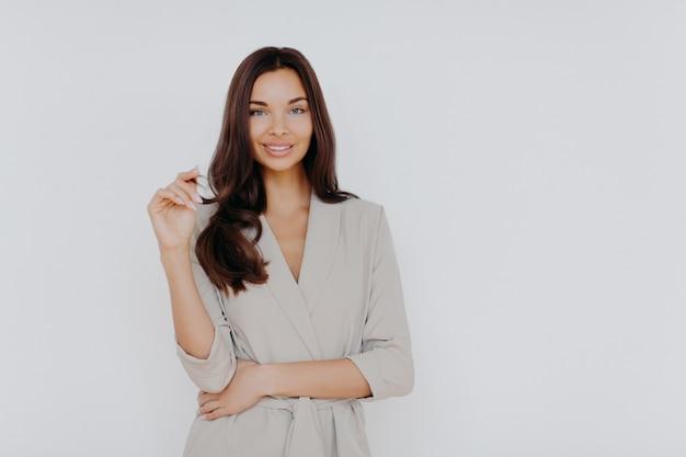 Pewna siebie piękna bizneswoman dotyka końcówek włosów