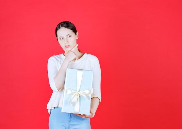Pewna siebie piękna dama trzymająca pudełko i myśląca