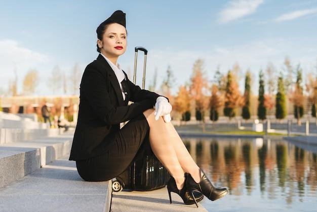 Pewna siebie piękna kobieta stewardessa w mundurze siedzi na schodach z walizką