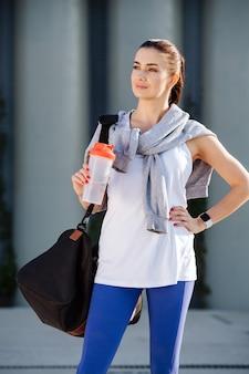 Pewna siebie piękna kobieta w sportowym stroju stojąca na ulicy trzymającej wodę