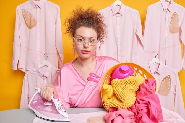 Pewna siebie, poważna pokojówka pozuje z koszem pełnym pralek, wyprane pomięte ubrania, nosi przezroczyste okulary, szlafrok wykonuje prace domowe. obowiązki domowe i odpowiedzialność