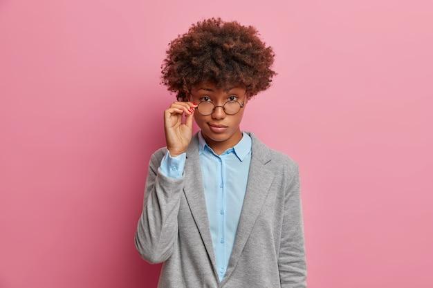 Pewna siebie, poważna reżyserka patrzy przez okulary, ubrana w formalne ciuchy