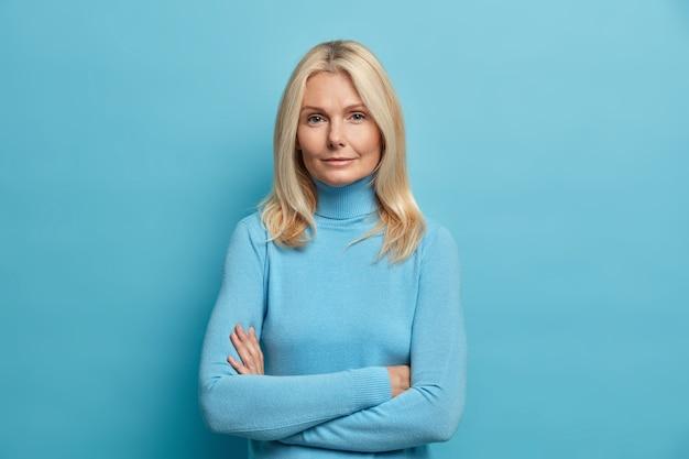 Pewna siebie poważna spokojna doświadczona blondynka w średnim wieku stoi z założonymi rękami