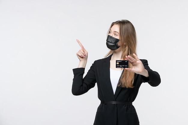 Pewna siebie przedsiębiorczyni w garniturze, ubrana w maskę medyczną i pokazująca kartę bankową skierowaną w górę na białym tle