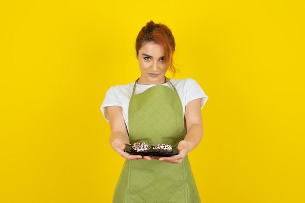 Pewna siebie ruda patrząca prosto w kamerę i trzymająca świeże ciasteczka