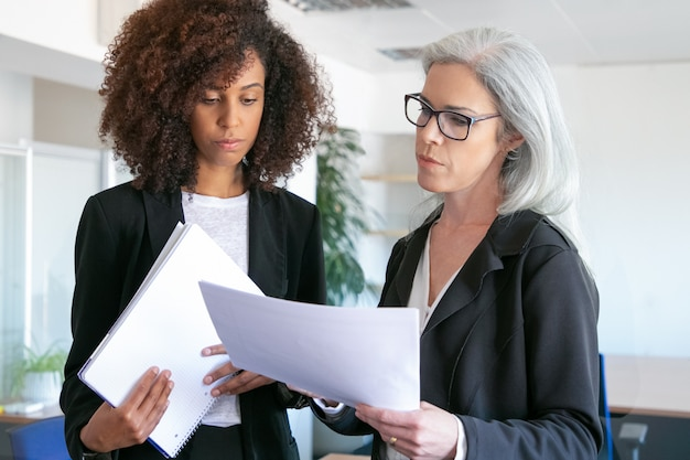 Pewna siebie skoncentrowana szefowa w okularach czyta raport. african american atrakcyjna udana młoda bizneswoman trzyma dokumentację dla menedżera. koncepcja pracy zespołowej, biznesu i zarządzania