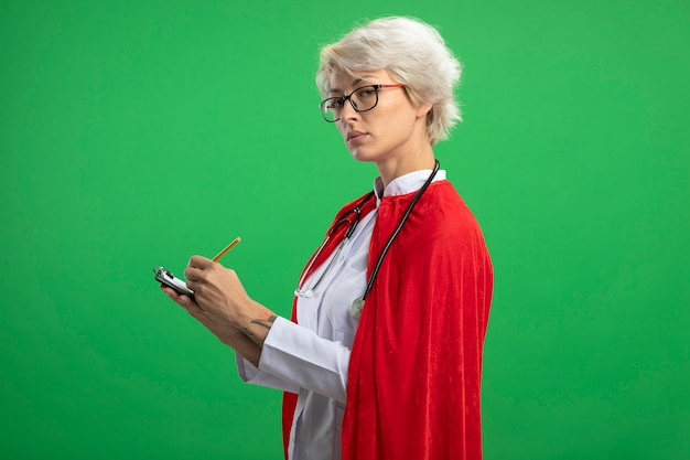 Pewna siebie słowiańska superbohaterka w mundurze lekarza z czerwoną peleryną i stetoskopem w okularach optycznych stoi bokiem trzymając schowek i ołówek patrząc na zieloną ścianę