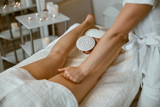 Pewna siebie specjalistka wykonuje antycellulitowy masaż nóg pięknej, zdrowej klientce rasy kaukaskiej