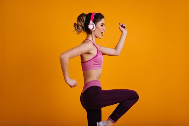 Pewna siebie sportowa kobieta trenująca w słuchawkach
