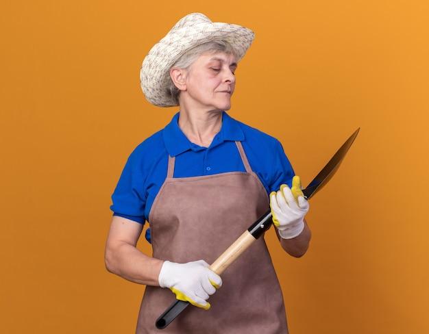 Pewna siebie starsza kobieta ogrodniczka w kapeluszu ogrodniczym i rękawiczkach, trzymająca łopatę i patrząca na nią