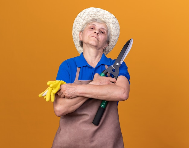 Pewna siebie starsza kobieta ogrodniczka w kapeluszu ogrodniczym stojąca ze skrzyżowanymi rękami trzymająca nożyczki ogrodnicze i rękawiczki