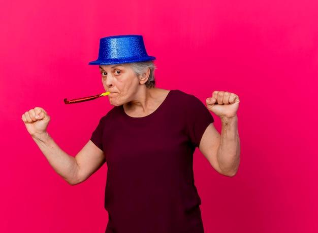 Pewna siebie starsza kobieta w kapeluszu imprezowym trzyma pięści w gwizdek na różowo