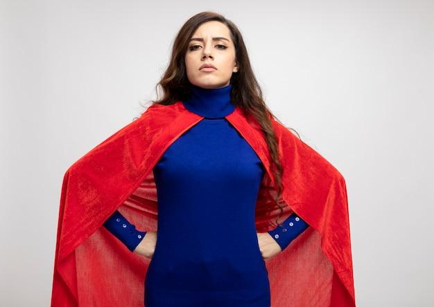 Pewna siebie superwoman w czerwonej pelerynie kładzie ręce na talii na białej ścianie