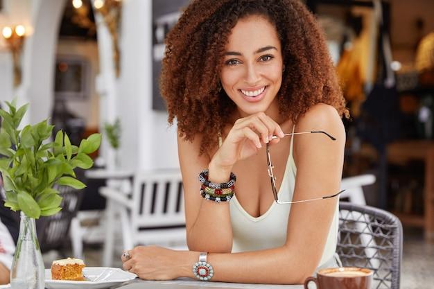 Pewna siebie, szczęśliwa, ciemnoskóra, młoda kobieta rasy mieszanej o kręconych włosach i wesołym wyglądzie, ubrana niedbale, odpoczywa w przytulnej kawiarni, smakuje pyszne ciasto
