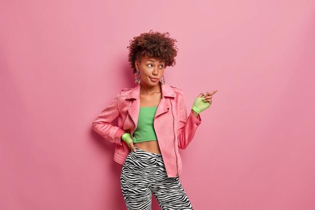 Pewna siebie szczupła afroamerykanka w stroju sportowym wskazuje na miejsce na kopię, wskazuje kierunek do klubu fitness, trzyma rękę na talii, prowadzi zdrową żywotność
