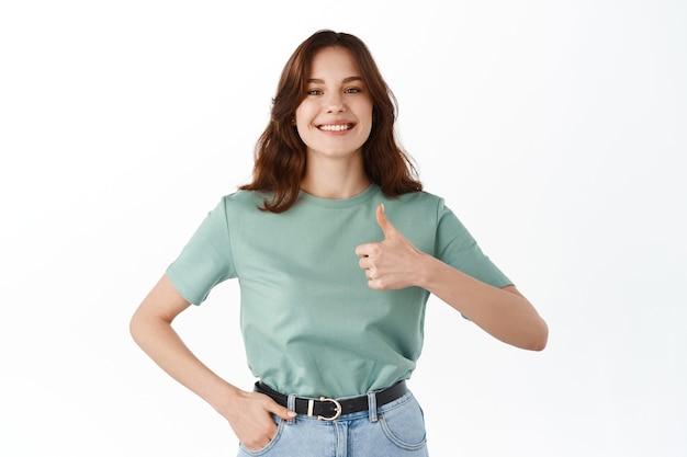 Pewna siebie uśmiechnięta kobieta pokazuje swoje wsparcie, kciuki w górę z aprobatą, chwalą dobrą robotę, dobrze wykonany gest, zgadzam się i aprobuję, stojąc przy białej ścianie
