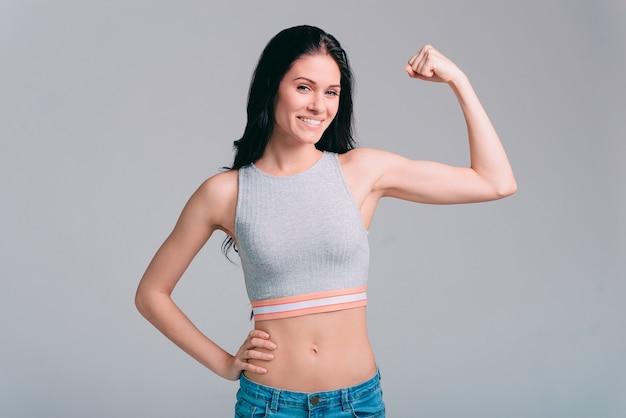 Pewna siebie w swoim ciele. atrakcyjna młoda sportowa kobieta pokazująca biceps i uśmiechająca się podczas stania