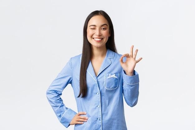 Pewna siebie wesoła azjatka w niebieskiej piżamie mruga i pokazuje dobry gest z zadowolonym, szczęśliwym uśmiechem, poleca dobrą jakość, gwarantuje doskonałą obsługę, jest usatysfakcjonowana na białym tle