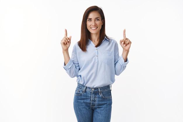 Pewna siebie wesoła dorosła kaukaska kobieta przedstawia własne biuro projektowe, wskazując w górę, górną przestrzeń kopii promocyjnej, uśmiechając się radośnie, pokazuj reklamę, sugeruj, polecaj promocję dobry produkt