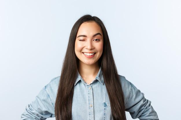 Pewna siebie wesoła freelancerka mruga i uśmiecha się, zachęca do zapisania się na kurs online, zaprasza pracę, stoi białe tło