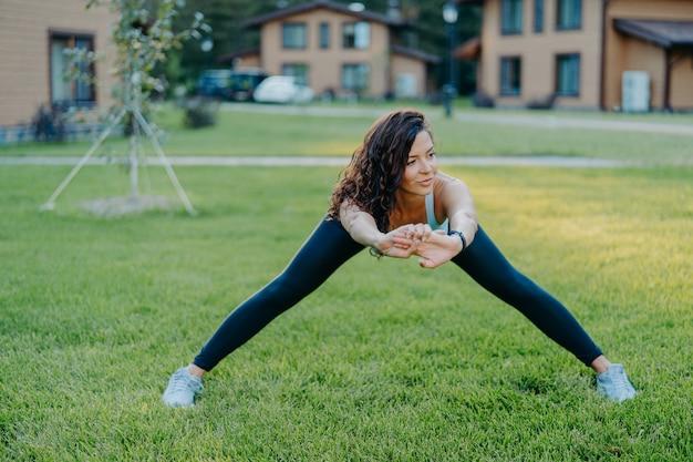 Pewna siebie wysportowana kobieta demonstruje swoją elastyczność