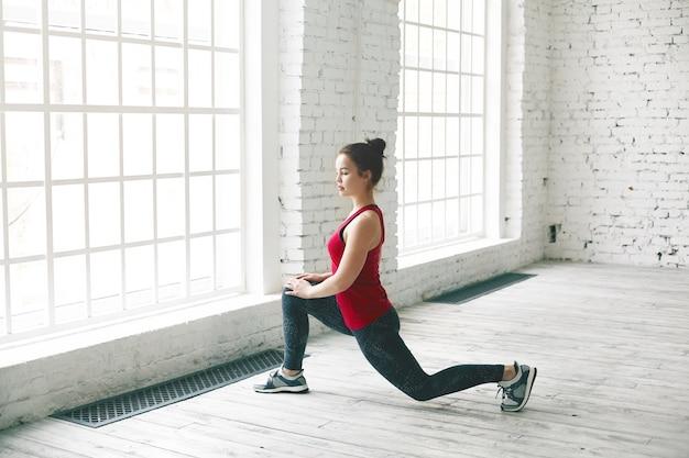 Pewna siebie zdeterminowana studentka z węzłem na włosach robi fizyczny trening w pomieszczeniu przed uniwersytetem. stylowa, sportowa młoda kobieta w trampkach i odzieży sportowej stojąca na niskim lonży, rozciągająca mięśnie nóg