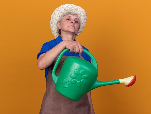 Pewna starsza kobieta ogrodniczka w kapeluszu ogrodniczym trzymająca konewkę