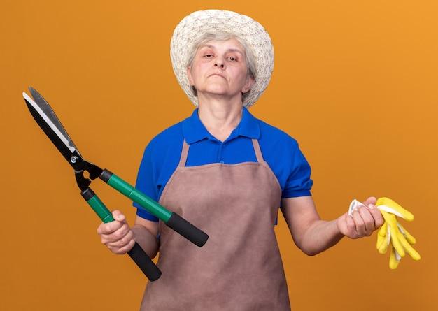 Pewna starsza kobieta ogrodniczka w kapeluszu ogrodniczym, trzymająca nożyczki ogrodnicze i rękawiczki odizolowane na pomarańczowej ścianie z miejscem na kopię
