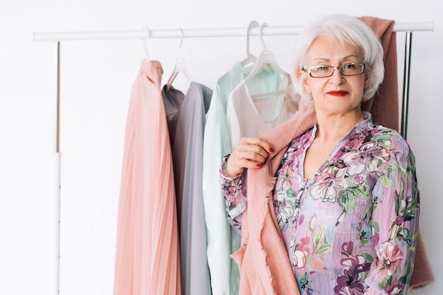 Pewna starsza pani w pracy. biznesowy butik mody. udane starsza pani pozowanie przez stojak z odzieżą w salonie.