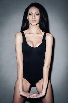 Pewna swojego idealnego ciała. piękna młoda afrykańska kobieta w czarnym stroju kąpielowym pozuje i patrzy na kamerę, stojąc na szarym tle
