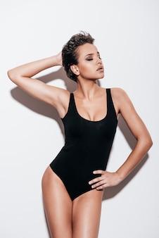 Pewna swojej doskonałości. piękna młoda kobieta z krótkimi włosami w czarnym stroju kąpielowym z zamkniętymi oczami podczas pozowania na białym tle
