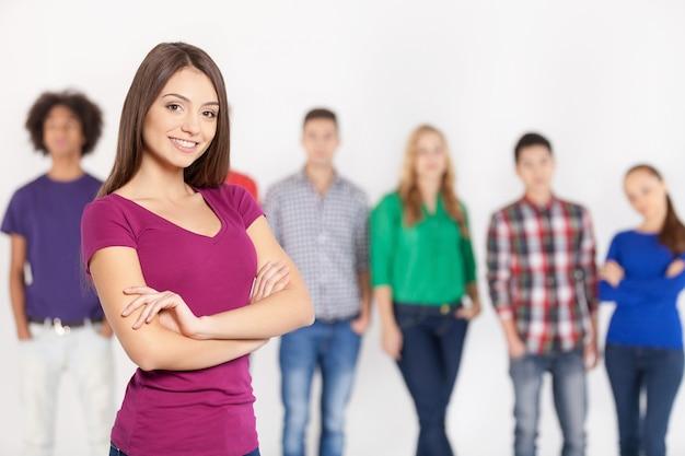 Pewna swojej urody. wesoła młoda kobieta trzymająca skrzyżowane ręce i uśmiechnięta, podczas gdy jej przyjaciele stoją w tle
