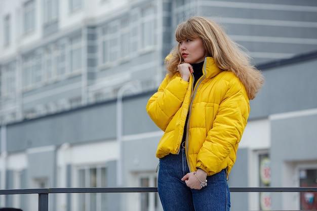 Pewna szczęśliwa piękna młoda hipster kobieta ubrana w żółtą kurtkę stojącą na ulicy miasta