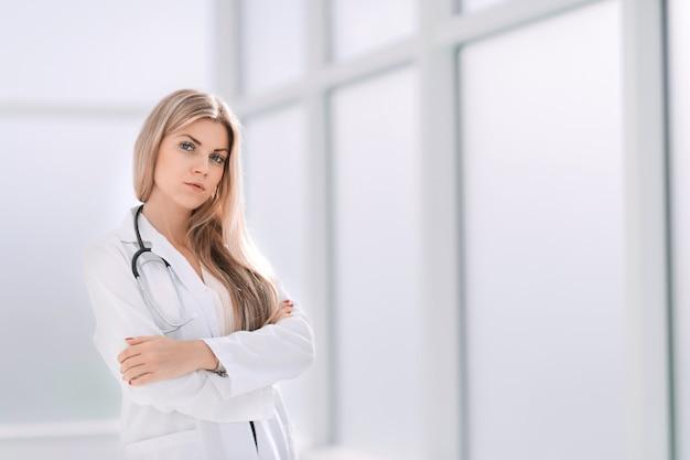 Pewna terapeutka stojąca przy oknie office.photo z miejsca na kopię