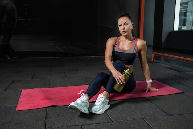 Pewna wysportowana dziewczyna odpoczywa po treningu na siłowni