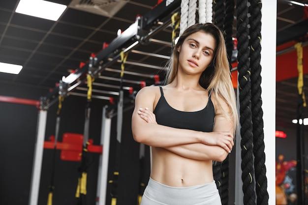 Pewna, wysportowana kobieca instruktorka fitness w dobrej kondycji, z skrzyżowanymi ramionami w fajnej pozie, w sportowej bieliźnie.