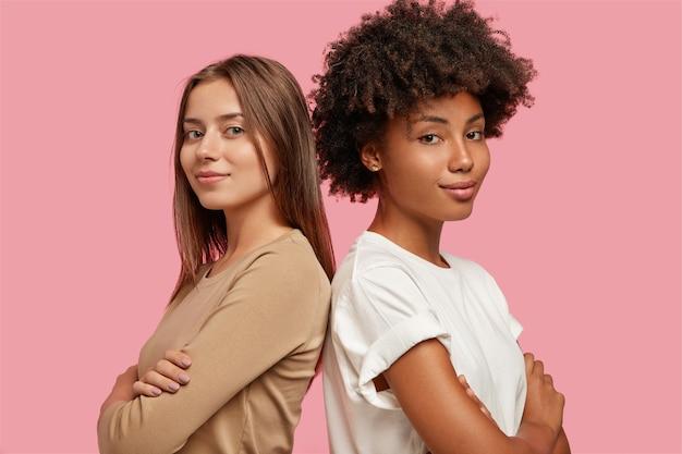 Pewne siebie młode kobiety rasy mieszanej stoją plecami do siebie, trzymając ręce skrzyżowane na piersi