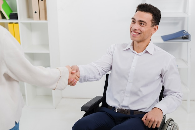 Pewni biznesmen siedzi na wózku inwalidzkim drżenie rąk z koleżanką