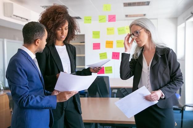 Pewni biznesmeni omawiają dane analityczne. odnoszący sukcesy doświadczeni menedżerowie w garniturach biurowych spotykają się w sali konferencyjnej i planują strategię. koncepcja pracy zespołowej, biznesu i zarządzania
