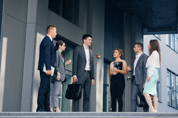 Pewni członkowie zespołu na schodach. biznesmeni i biznesmeni w formalnych garniturach rozmawiają na tle nowoczesnego biurowca. mężczyźni i kobiety rozmawiają o biznesie. grupa sześciu osób.